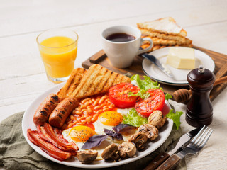 Full English Breakfast including sausages, grilled tomatoes and mushrooms, egg, bacon, baked beans, bread with orange juice