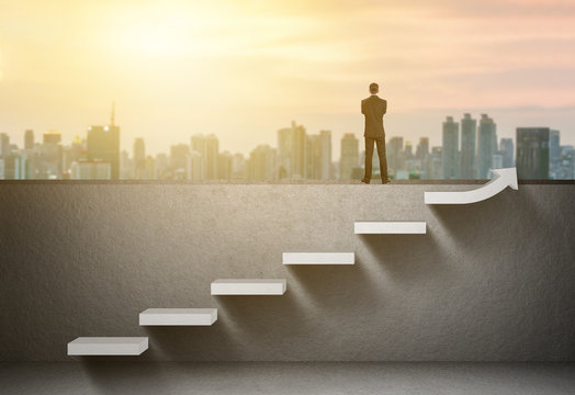 Businessman stand on rising arrow graph on staircase with city sunrise background