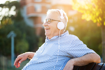 Outdoor portrait of senior man who is listening music on headphones.