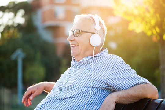 Outdoor portrait of senior man who is listening music on headphones.