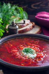 Hot soup with beets and sour cream in a clay bowl, selective focus