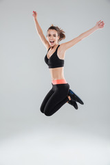 Full length image of happy jumping fitness woman