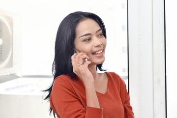 Smiling asian woman making a call