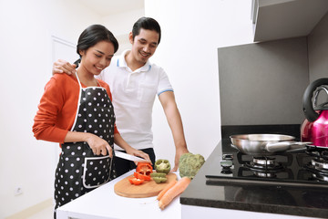Portrait of asian couple smiling and cooking together