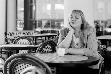 A woman of size plus a US or European saithe sitting in a restaurant drinks coffee in a good mood. A young girl with excess weight, stylishly dressed in the center of the city is waiting for a friend