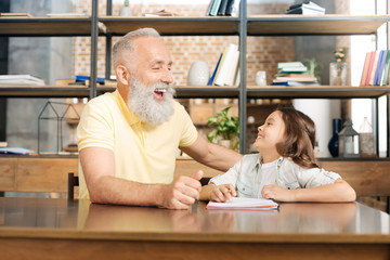 Grandfather and granddaughter laughing happily at the table