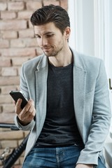 Casual man holding mobilephone