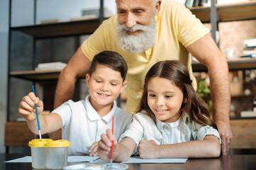 Grandfather watching grandchildren washing brush and choosing color