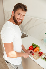 Vertical image of smiling bearded man cuts vegetables on kitchen