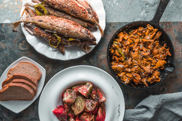 Fried chanterelles, fish on a plate, tomatoes and bread