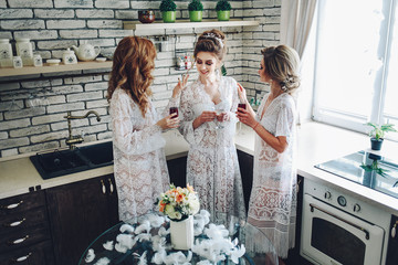 A cute young bride with cute girlfriends in a boudoir in the morning in a bright room