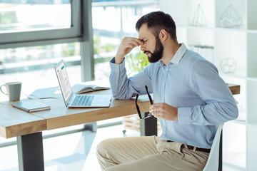 Tired businessman pinching bridge of nose
