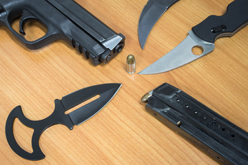 Pistol cartridges bullet and knife on wooden table, set of combat weapon concept.
