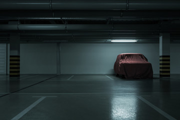 Red covered vintage car in empty underground parking background with copy space