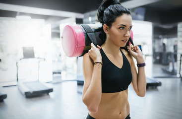 Close-up shot of brunette sporty woman working out with sandbag while exercise for butt legs in fitness club or gym. Attractive athletic female doing hard workout with weight training with copy space.