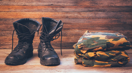 old leather black men boots and military uniform on a wooden background front view close-up