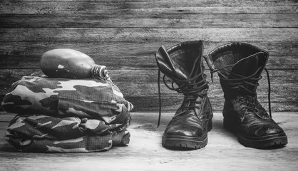 old leather black mens boots, military uniform and flask for water on a wooden background front view close-up, black and white photo