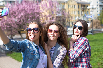 Happy teenage girls hawing fun spend time together in the city park