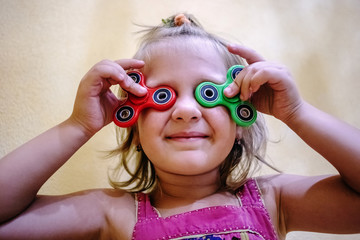 Cute little girl holds two fidget spinners on her face