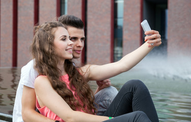 Young couple sitting in town outdoor with mobile phone taking selfie