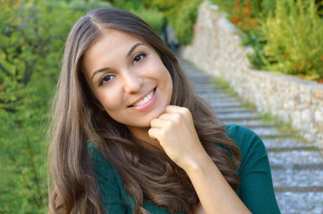 Portrait of young brunette woman sitting outdoors. Girl is supporting her chin by fist.