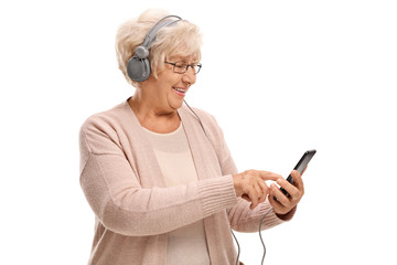 Elderly woman with headphones listening to music on a phone