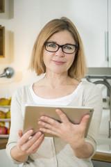 Senior woman in kitchen holding digital tablet