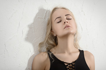 sensual young woman with closed eyes near white wall background