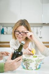 Senior woman reading tag on oil bottle