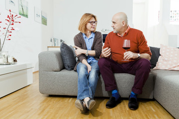 Senior couple drinking red wine at home