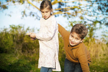 Girl and boy playing outdoors, portrait