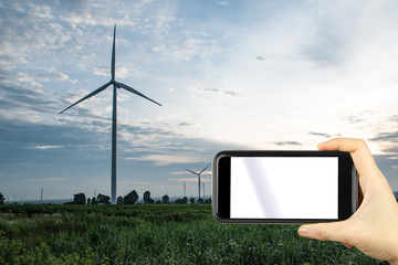 hand shoting by smart phone with background wind turbines windmill.