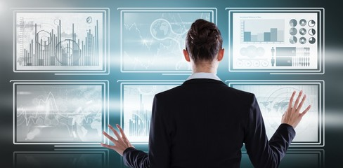 Composite image of rear view of businesswoman using digital