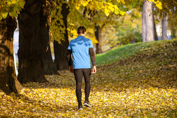 Male runner walking among autumn leaves