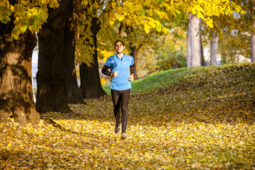Male runner jogging in autumn park