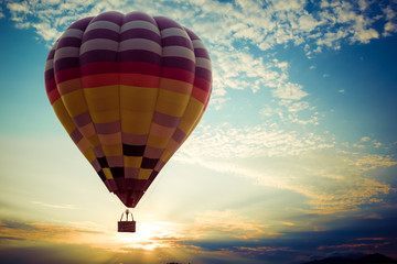 Colorful hot air balloon flying on sky at sunset. travel and air transportation concept - vintage and retro filter effect style