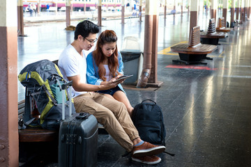 Tourists couple travelers are traveling and looking gps and map from smartphone and tablet at train station railway platform. Traveling concept