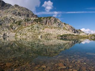 Mountains reflect on small alpine lake on the Bergamo Alps, northern Italy.