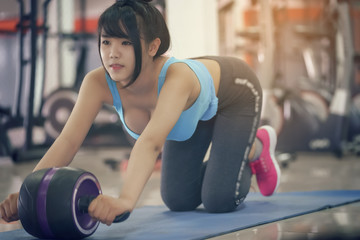 Young woman exercise with roller wheel at the gym.