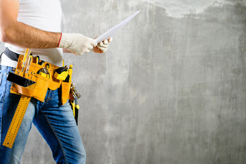 unidentified handyman with hand on waist and tool belt with construction tools holding the project plane against grey background, copyspace. DIY tools and manual work concept