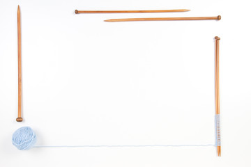Knitting needles and blue yarn ball frame on white background