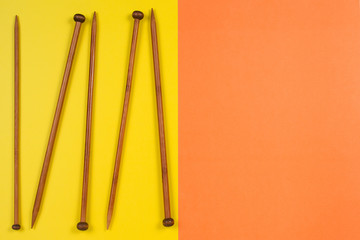 Variety of bamboo knitting needles in different sizes on yellow and orange background