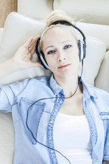 Blond woman listening to music with headphones
