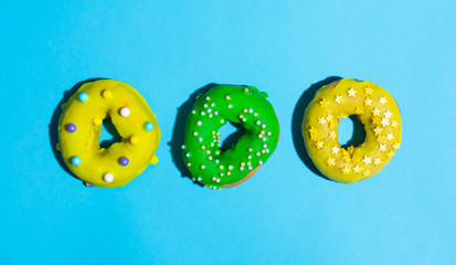 Colorful glazed donuts on a bright blue background
