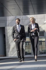 Business partners walking against office building