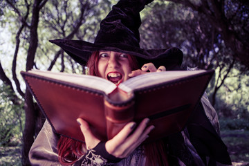 Toned photo of witch with book of spells