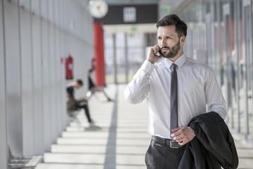 Businessman using phone in modern lobby