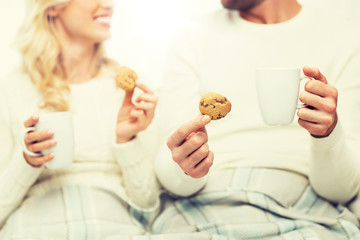 close up of happy couple with cookies and tea cups