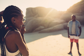 Beautiful woman taking picture of her boyfriend at beach