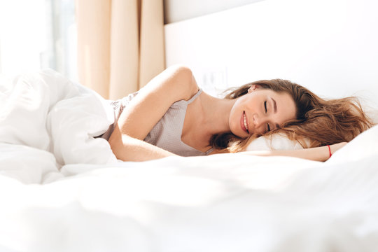 Smiling pretty lady lies in bed indoors. Eyes closed.